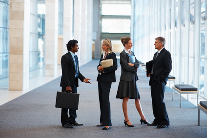 Full length image of business colleagues standing and discussing at the hallway