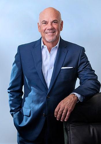 Imagen de Jay Cohen apoyado contra la silla de su oficina, fondo azul